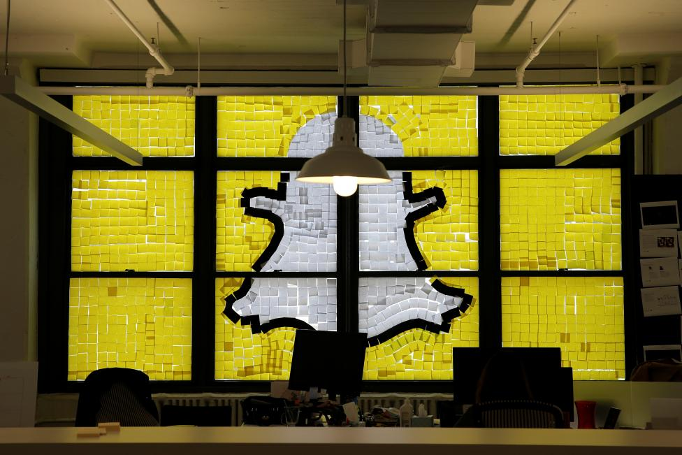 "An image of the Snapchat logo created with Post-it notes is seen in the windows of Havas Worldwide at 200 Hudson Street in lower Manhattan, New York, May 18, 2016, where advertising agencies and other companies have started what is being called a ""Post-it note war"" with employees creating colorful images in their windows with Post-it notes. REUTERS/Mike Segar"